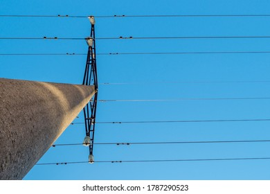 Concrete round electric pole with transverse metal diamond-shaped holders structure with clusters of insulators, to which horizontal main electrical high-voltage wires attached by means of tripwires