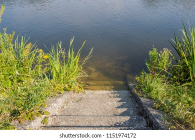 A concrete staircase leads to the water of a dam