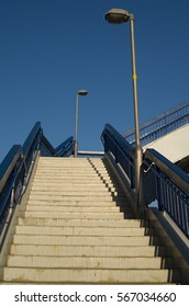 Concrete stairs with blue railing and two lamps with sky in background