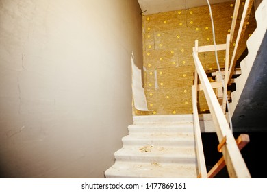 Concrete stairs construction at new building. Interior with flight of stairs and mineral wool insulation of wall