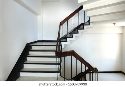 concrete stairs are wooden handrails. ladder in the building. Empty modern building stairway