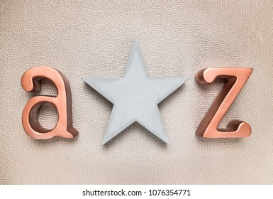 Concrete star and metal letters A and Z, on leather background.
