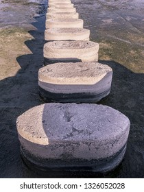 Concrete stepping stones disappearing in perspective over water vertical image