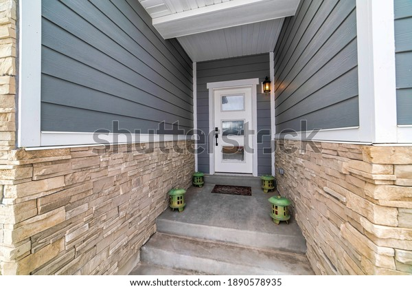 Concrete steps and lanterns at the home entrance with glass paned front door