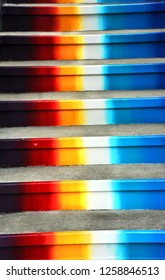 Concrete steps painted colors of the rainbow, climb heavenward.