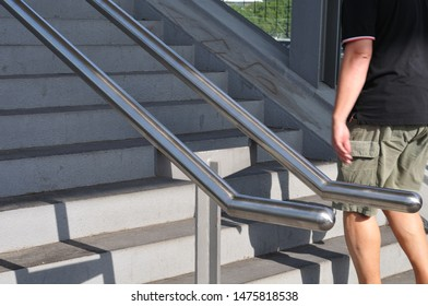 concrete steps with railing of stainless steel leading to pedestrian bridge over railway tracks with unrecognizable person
