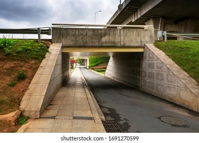 Betonstruktur und Asphaltstraßen unter der Überführung in die Stadt