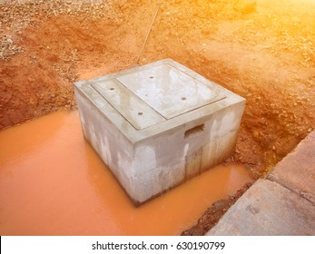 Concrete sump for drainage system construction. Flooded drainage pond after heavy rain.