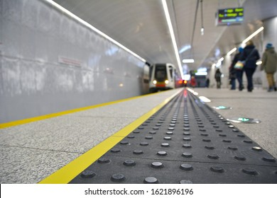 Concrete tactile strips with an yellow line - for visually impaired (handicapped) and people with blindness - on an underground station, with a blurred arriving subway train and background