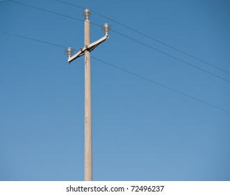 Concrete telegraph pole against blue sky