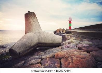 Concrete tetrapod breakwater on a pier in Swinoujscie at sunset, color toned picture, Poland.