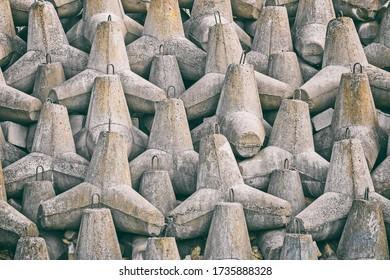 concrete tetrapod breakwaters lie all along the coast, the coast breakwaters protecting from large waves, toned image - Shutterstock ID 1735888328
