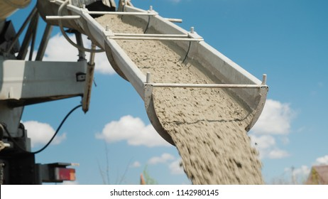 The concrete is unloaded from the concrete mixer. Against the blue sky. Construction of country houses.