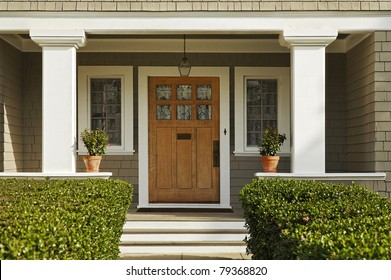 A concrete walkway bordered with hedged shrubs leads to the front door of a home. There are windows on either side of the door. Horizontal shot.