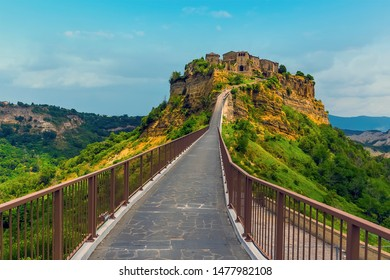 The concrete walkway leads to the rock outcrop on which is perched the settlement of Civita di Bagnoregio in Lazio, Italy in summer