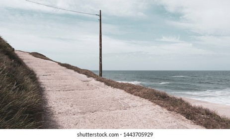 Concrete walkway & wooden post at the beach with view of the Atlantic ocean. Taken in Praia das Maçãs, Portugal on a sunny summer day.