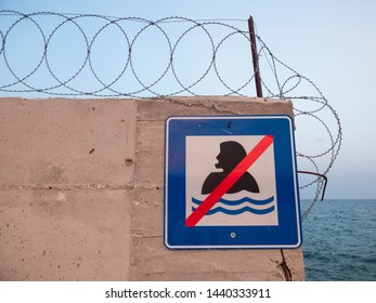 """Concrete wall with barbed wire atop and sign """"Swimming prohibited"""""""