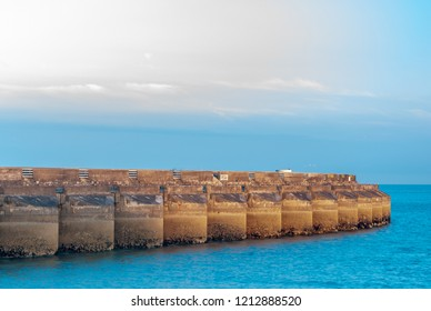Concrete wall of a marina in late afternoon sunlight