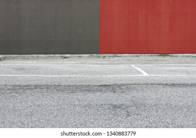 Concrete wall painted half red and half gray with an asphalt road in front. Background for copy space