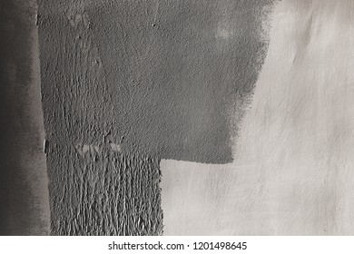 Concrete wall partially painted in gray with a paint roller. Paint texture in side sunlight
