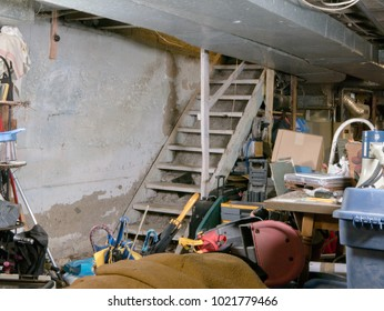 Concrete wall provides text space  inside residential unfinished basement being used for storage, cluttered with boxes, bins, and other random forgotten items of a disposable consumerist lifestyle