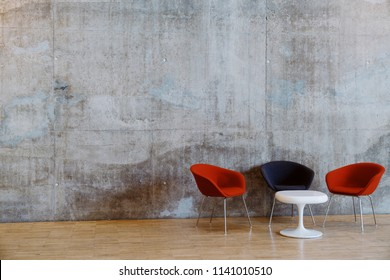 Concrete wall and white coffee table with red and navy chairs