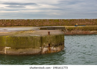Concrete wharf. Yellow and brown steel bitts in the port in the Peterhead, Aberdeenshire, Scotland, UK