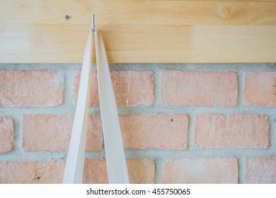 Concrete and wooden wall with wall hanger.