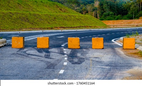 A concrete yellow painted road block kept over a newly tarred road near a grassy hill with fog raising from the dense forest in the background.