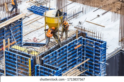 Concreting work at the construction site. Construction workers pour liquid concrete from cement concrete hopper to formwork installation.