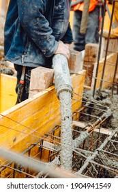Concreting work at the construction site. Construction workers pour liquid concrete from cement concrete hose