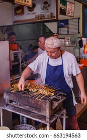 Concubine Lane, Ipoh June 9th 2017 : Famous traditional Kajang Satay hawker roasting skewered chicken and pork meat satay on charcoal fire, one of the famous tourist food attractions in Ipoh