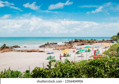 Conde - PB, Brazil - February 22, 2019: Beach umbrellas and tourists at Praia de Tambaba beach, Costa do Conde. Beautiful Brazilian northeast beach.