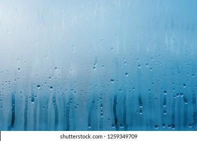 Kondensation auf dem klaren Glasfenster.Wasser fällt. Regen. Abstrakte Hintergrundtextur