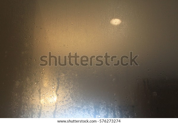 Condensation on the glass with yellow light in the evening.