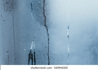 Condensation on the windows a strong, high humidity in the room, large water droplets flow down the window, cold tone