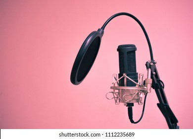 Condenser Microphone with holder and jack connected in pink background and copy space on right of picture