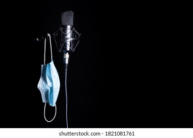 Condenser microphone in its holder next to a mask hanging on the holder, black background