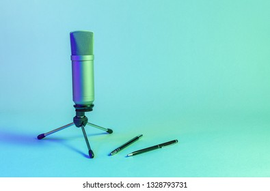 Condenser microphone with holder on neon, blue background