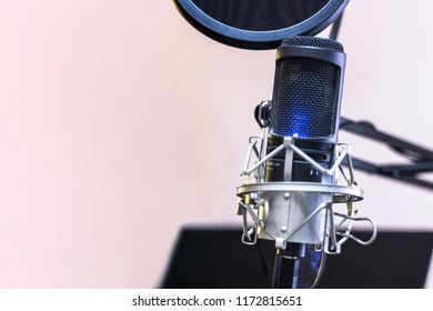 Condenser microphone on holder and pop filter with blue light swith on for voice over on blurred monitor background and copy space