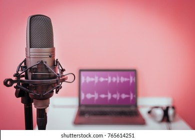 condenser microphone on laptop computer with waveform on screen and headphone background, home studio & recording concept