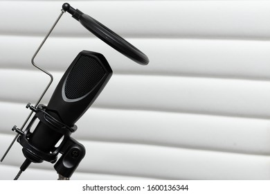 Condenser microphone placed on a tripod with white acustic panels in the  background in a music studio, ready for recording.