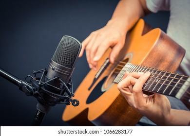 condenser microphone recording acoustic guitar sound in music studio