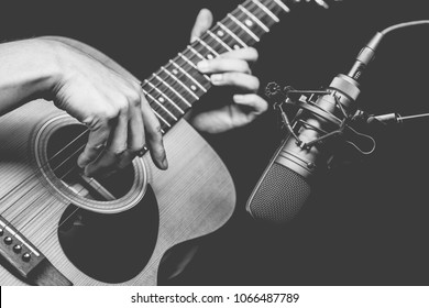 condenser microphone recording acoustic guitar sound in music studio