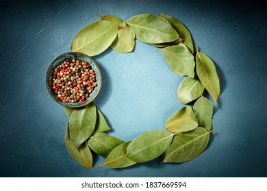 Condiments background with copy space. Bay leaves and peppercorns, forming a wreath with a place for text, overhead shot on a blue background