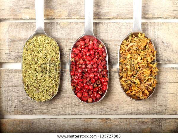 Condiments in three spoons on wooden background