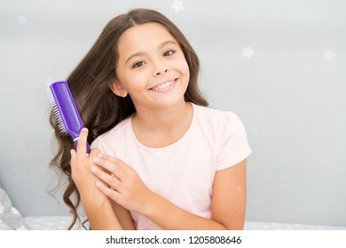 Conditioner or mask organic oil comb hair. Beauty salon tips. Girl long curly hair grey interior background. Child curly hairstyle hold hairbrush or comb. Apply oil before combing hair. Healthy hair.