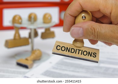 conditions printed on rubber stamp in hand
