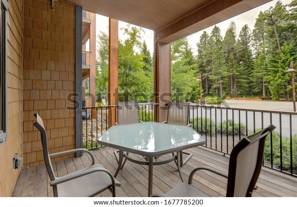 Condo style luxury vacation living in apartment building balcony with pine trees views and table with four chairs.