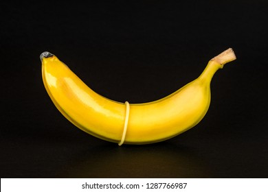 Condom and banana on black background close up.